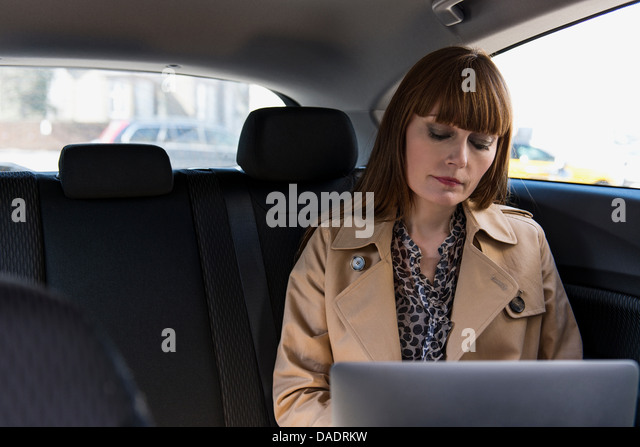 Business woman with laptop in car - Stock-Bilder