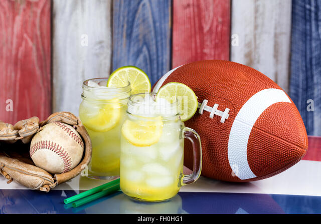 Jar glasses filled with cold lemonade with sporting items.  Faded wooden boards painted red, white and blue in background. - Stock-Bilder