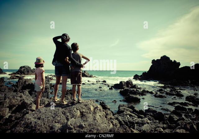 Mother, son, daughter, look out over southern ocean, Cape Palliser, New Zealand. - Stock Image