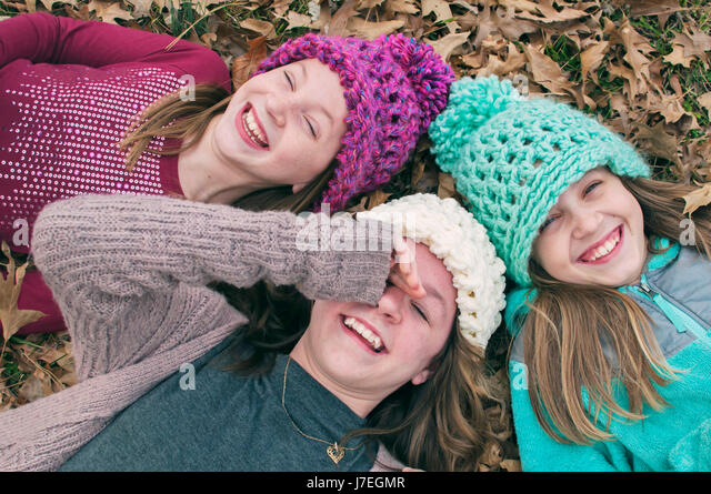 Three girls laughing wearing hats - Stock Image
