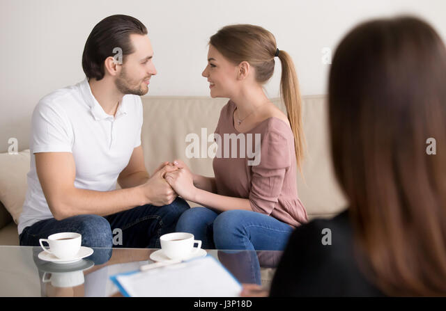 Happy smiling young couple holding hands, consulting psychologis - Stock Image