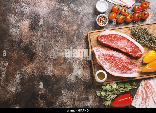 Fresh raw Prime Black Angus beef strip steaks on cutting board over dark rustic concrete background, top view. Ingredients - Stock Image