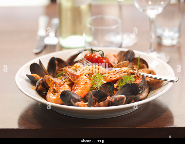 Bowl of prawns and mussels in restaurant - Stock Image