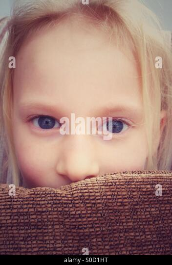 Young girl peering over cushion - Stock Image