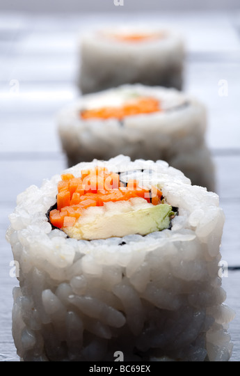 shallow focus vertical macro of 3 rolls of sushi - Stock Image