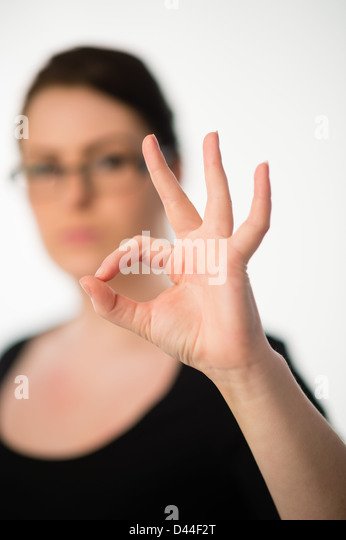 A young woman, brown hair, signing OK with her fingers and thumb UK - Stock Image