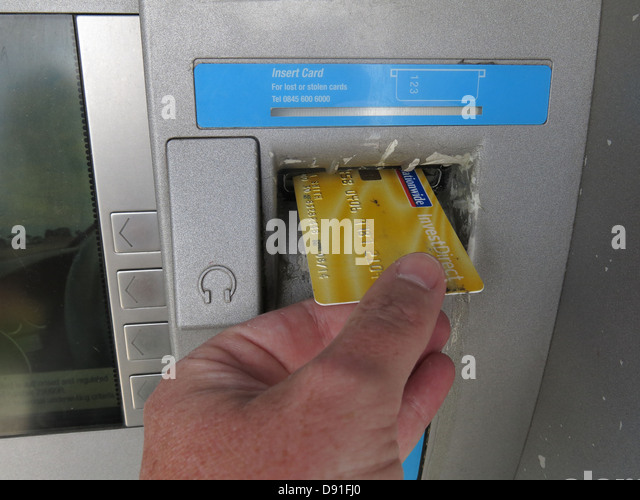Putting a Nationwide account card into a co-op cash machine yellow - Stock Image