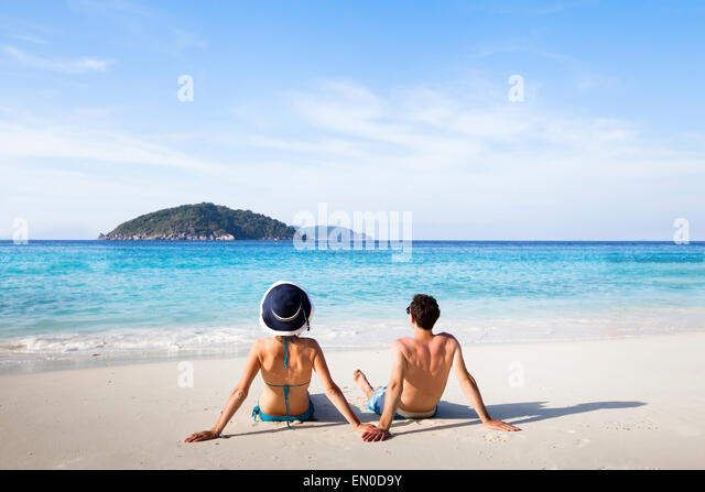 honeymoon destination, young happy couple relaxing on paradise beach - Stock Image