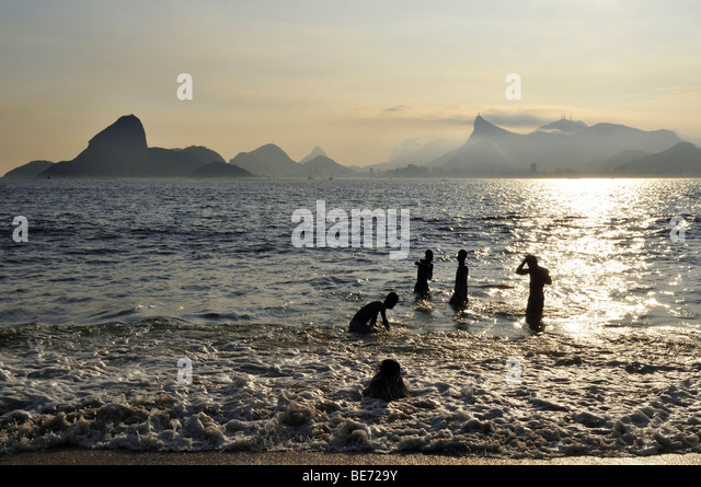Young people in the ocean and view of the Sugarloaf Mountain and Corcovado Mountain, Niteroi, Rio de Janeiro, Brazil, - Stock-Bilder