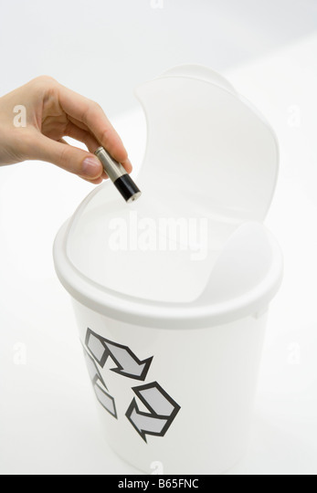 Hand placing battery into recycling bin, close-up - Stock Image