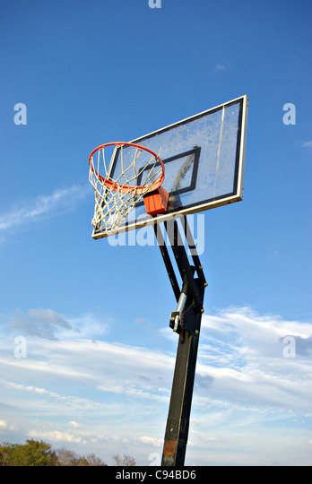 A basketball goal with the sky for a background out in the country. - Stock Image