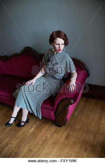 Woman in vintage 1940s dress sitting on sofa - Stock-Bilder