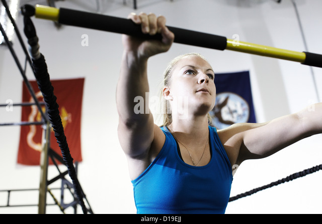 Woman working out in gym with exercise bar and resistance cord - Stock Image