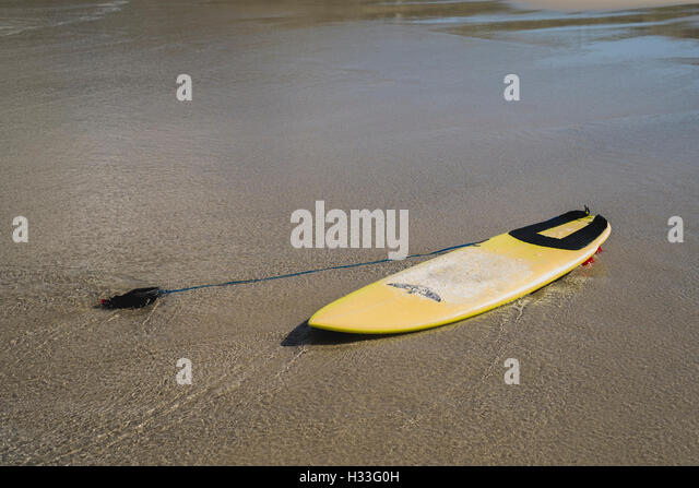 A lone surfboard left on the beach at Sennen Cove, Cornwall - Stock Image