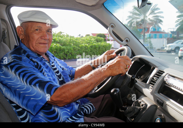 Curaçao Netherlands Antilles Dutch Willemstad Otrobanda shuttle driver chauffer senior elderly man cap printed - Stock Image