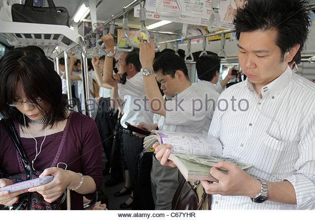 Tokyo Japan Yurakucho JR Yurakucho Station Yamanote Line Asian man woman crowded standing commuters train car strap - Stock Image