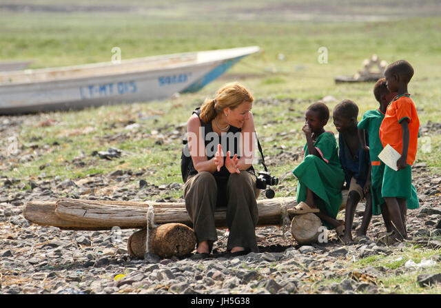 LOIYANGELENI, KENYA - May 18. A tourist chats with children by the shores of Lake Turkana during the Lake Turkana - Stock Image