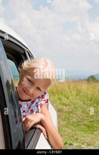 portrait of young girl looking out of car window - Stock Image
