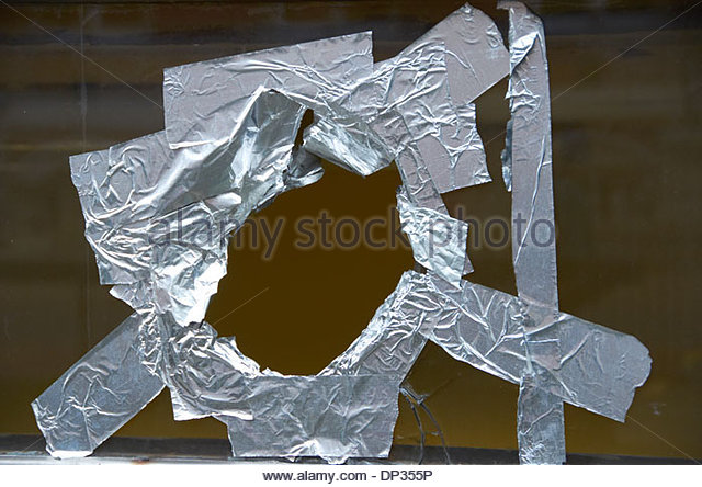 Badly taped up hole in a window. - Stock Image