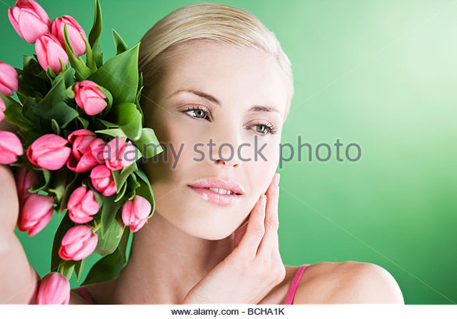 A young woman holding a bunch of pink tulips, thinking - Stock Image