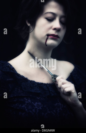 a woman in a dark dress is holding a dagger at her throat, having blood dripping out of her mouth - Stock Image