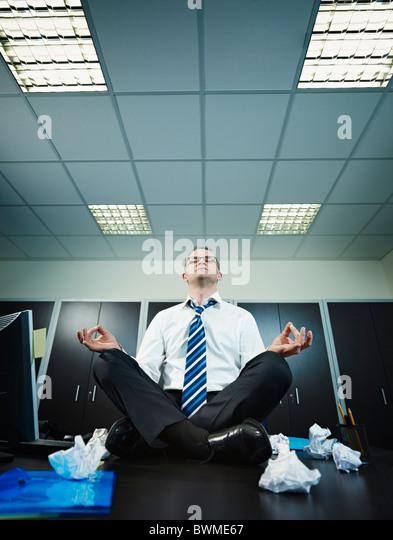 mature businessman meditating on desk - Stock Image