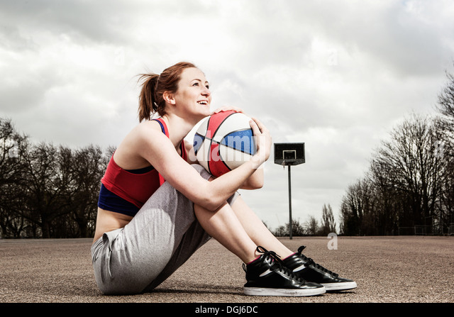 Woman hugging netball to chin - Stock Image