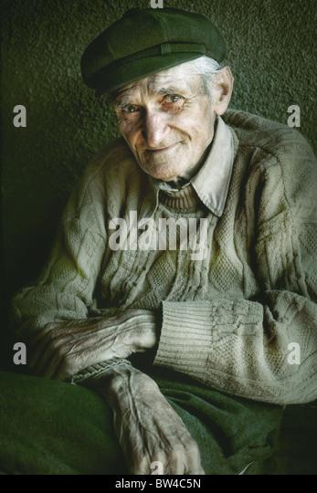 Artistic portrait of old senior man with wrinkled hands - Stock Image