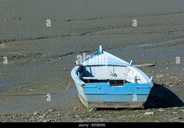 Rowboat stranded on mud flat - Stock Image