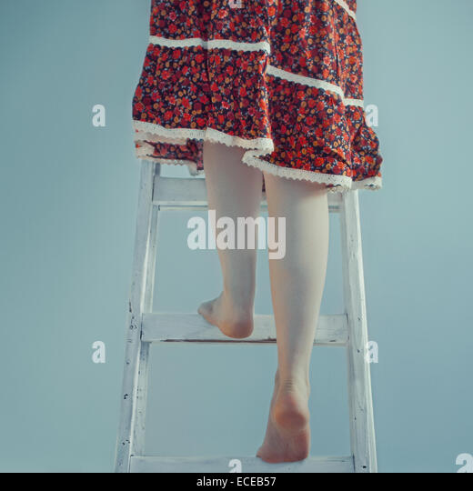 Woman climbing up a ladder - Stock Image