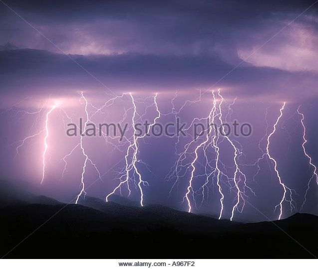 Lightning bolts dance across the Rincon Mountains Tucson Arizona during a severe monsoon type thunderstorm. - Stock Image