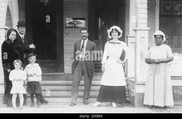 A family (consisting of a mature woman, a mature man, a young girl, and a young boy) and a boarding house staff - Stock Image