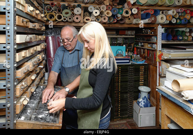 Senior man and young woman selecting book letterpress in traditional bookbinding workshop - Stock Image