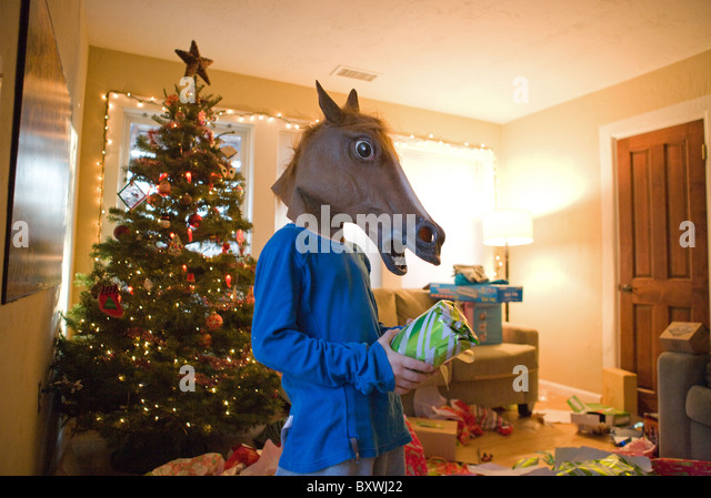 A child wearing a horse head mask while opening in a Christmas present in the living room on Christmas day. - Stock Image
