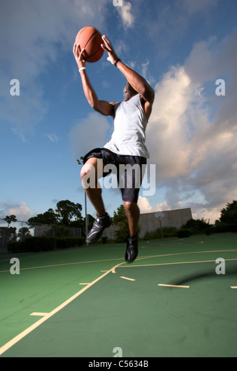 male making vertical jump during outdoor basketball game - Stock Image