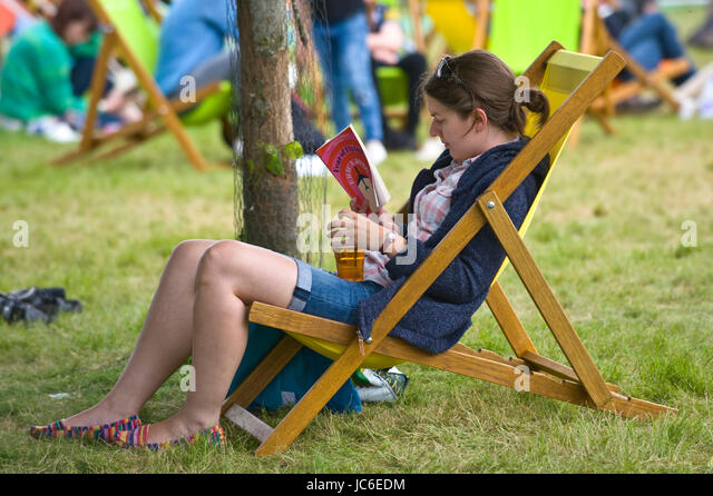 Young woman reading book relaxing in deckchair at Hay Festival of Literature and the Arts 2017 Hay-on-Wye Powys - Stock Image