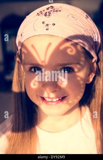 Portrait of smiling little girl with butterfly shaped shadow on her face - Stock Image