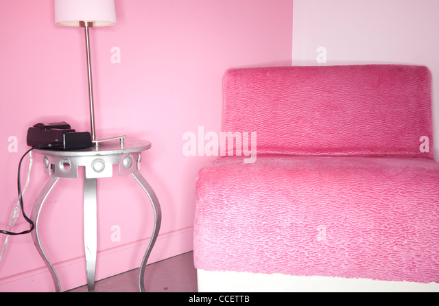 Interior of rock motel with chair and lamp - Stock Image