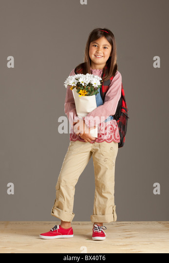 A Girl With A Backpack Holding A Bouquet Of Flowers - Stock Image