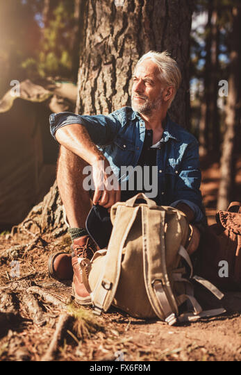 Portrait of senior man looking away while sitting by a tree. Senior man with a backpack outdoors on a summer day. - Stock Image