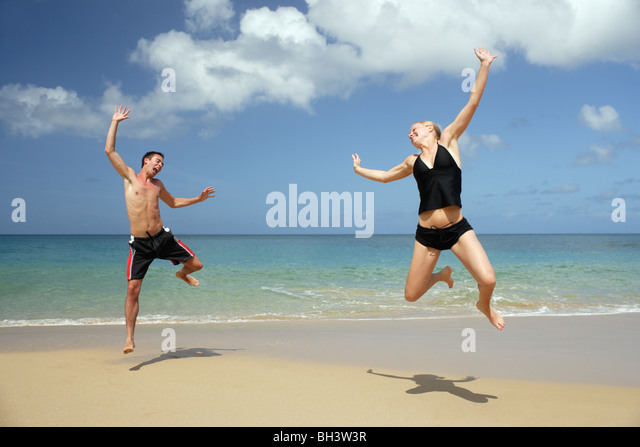 Young couple leaping on a tropical beach, laughing - Stock Image