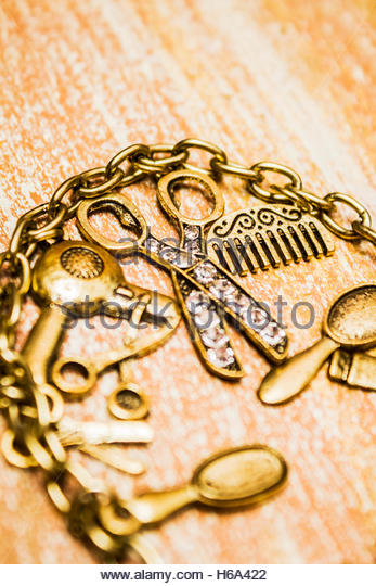 Opulent hairstyle treatment concept on a bangle of golden hairdresser styling tools. Gold class hair style background - Stock Image