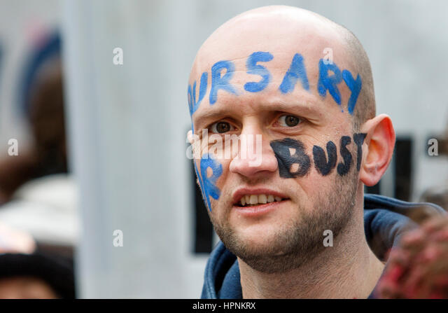 NHS worker protesting about NHS bursay cuts is pictured as he takes part in a save our NHS protest march and demonstration - Stock Image