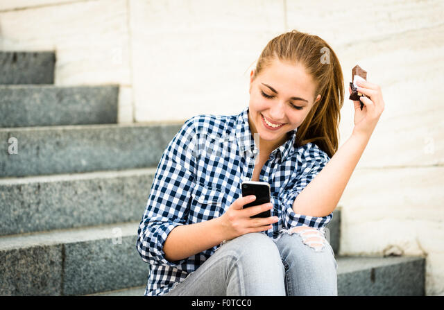 Teenager - young woman eating chocolate in street and looking in phone - Stock Image