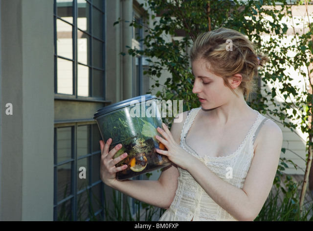 Young woman holding vegetable waste - Stock Image