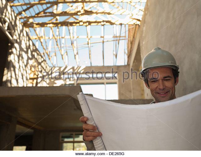 Architect reviewing blueprints at construction site - Stock-Bilder
