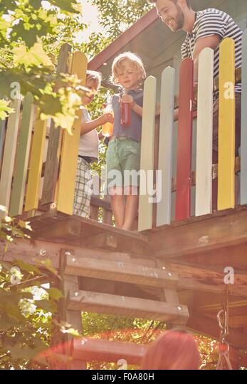 Father and sons in tree house, sons enjoying a drink - Stock Image