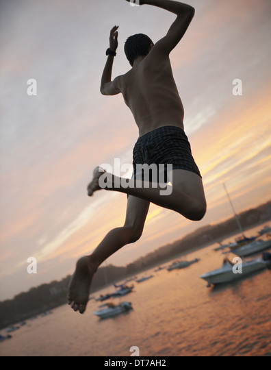 A boy leaping off the dock into the water at sunset on the coast USA - Stock Image