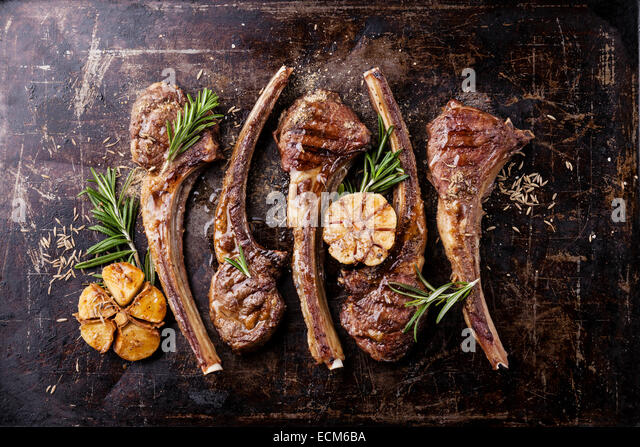 Roasted lamb ribs with spices and garlic on dark textural background - Stock Image