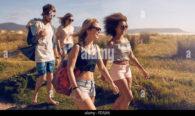 Portrait of group of friends going to on the beach. Mixed group of friends walking on the beach on summer day. - Stock-Bilder